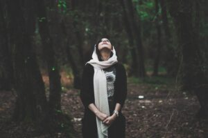 Woman looking up while standing in a forest and contemplating her self-awareness.