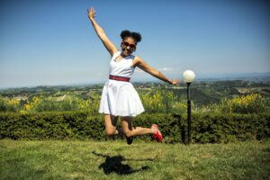 Woman jumping for joy because she is living a happy and healthy life.