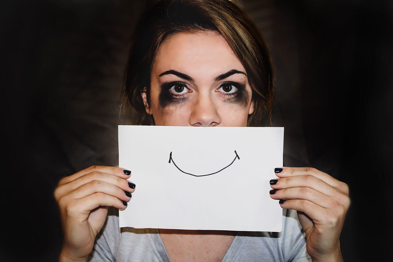 A woman trying to cover up her sadness about her unhealthy marriage with a smile.
