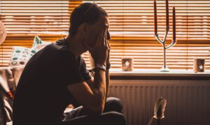 Man sitting with his hands covering his eyes as he struggles with life after divorce.
