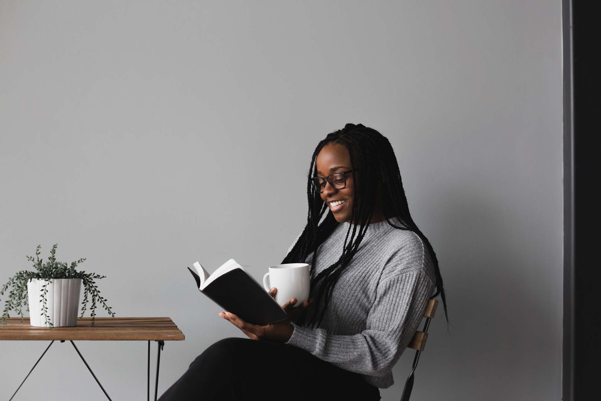 Woman sitting and smiling as she reads finding-happiness quotes.