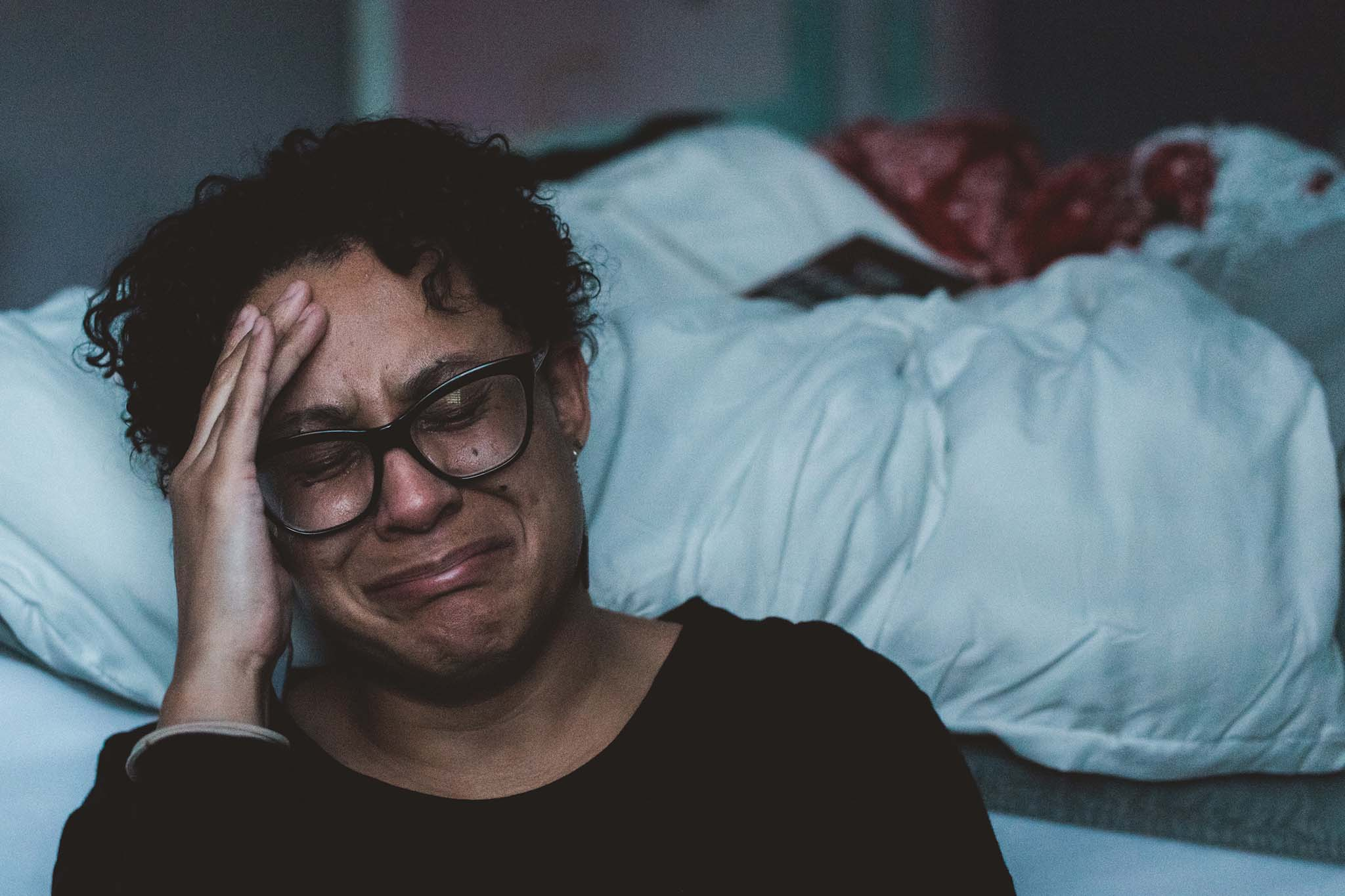 Woman sitting on the floor next to her bed crying about her miserable marriage