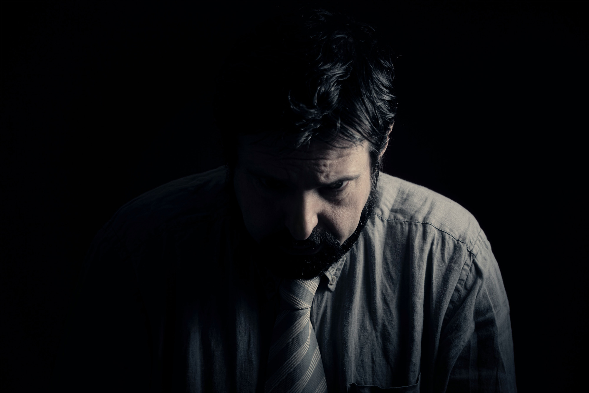 Sad man sitting in the dark contemplating how to survive his unhealthy marriage.
